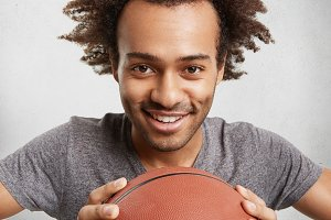 People, active lifestyle and sport concept. Cheerful male teenager with Afro hairstyle, keeps basket ball, rejoice winning of game. Happy man being glad to buy new equipment for playing basketball