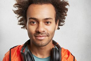 Close up portrait of attractive man with Afro hairstyle, stubble, wears orange anorak, has modern headphones on neck, going to listen music, enjoys calm atmosphere. People, leisure, lifestyle