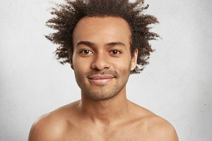 Close up portrait of condifent dark skinned male with bristle has crisp hair and full lips, being naked, glad to recieve congratulations on birthday from relatives and friends. Positive human emotions