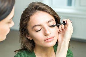 Brush applying beige makeup