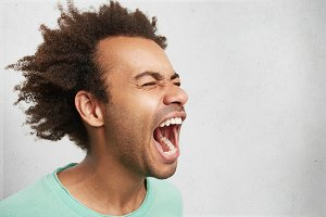 Horizontal portrait of man with dark skin and Afro hairstyle screams in despair, opens mouth widely, being in panic. Frustrated mixed race man poses against white studio background with copy space