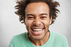 Portrait of cheerful overjoyed male with bushy hairdo, smiles happily, being glad to find out about successfully passed exam, isolated over white background. Positiveness and gladness concept