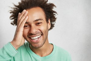 Cheerful dark skinned male with Afro hairstyle keeps hand on head, laughs as has fun with friends, isolated over white background. Happy smiling guy has happy expression, hears pleasant news