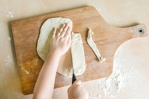 children's hands cutting raw rolled dough