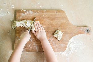 children's hands cutting raw dough