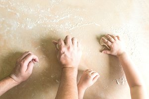 Children's and dad's hands makes raw dough