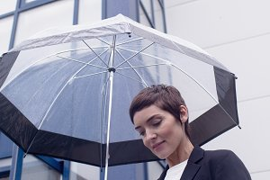 Businesswoman using mobile phone while holding umbrella