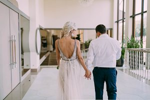 Newlyweds looking each other with tenderness and holding hands.Beautiful tanned bride in a beige fitting dress and groom in a white shirt. Wedding