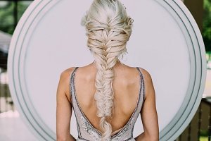 Creative braid hairstyle. Bride back with the open back beige fitting dress.