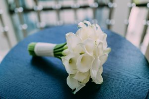 Beautiful wedding bouquet of calla flowers on blue table background. Artwork. Soft focus on a bouquet