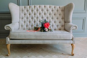 Rustic wedding bouquet with white roses and crimson peonies on a luxury cream sofa. Close-up.