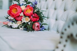 Rustic wedding bouquet with white roses and crimson peonies on a luxury cream sofa. Close-up. Side view