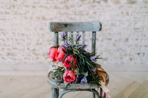 Rustic wedding bouquet with white roses and crimson peonies on the aged gray wooden chair. Indoors.