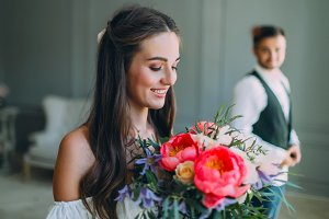 Close-up portrait of cheerful, young bride with a wedding bouquet on blurred groom background. A happy girl with a bunch of flowers