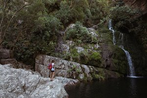 Woman standing near waterfall
