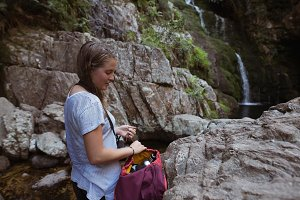 Female hiker standing near waterfall with a bag