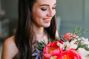 Cheerful, young bride holds a rustic wedding bouquet with white roses and crimson peonies. Close-up portrait. A happy girl with a bunch of flowers
