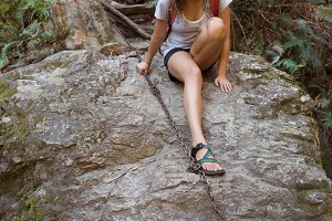 Female hiker holding the chain while climbing down the rocks