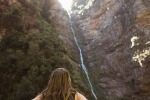 Rear view of woman looking at the waterfall