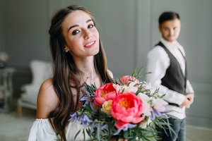 Close-up portrait of cheerful, young bride with a wedding bouquet on blurred groom background. A happy girl posing with a bunch of flowers