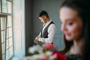 Handsome groom is preparing for wedding day on a background of blurred bride with a bouquet. Man in the festive clothes near a panoramic window. Artwork