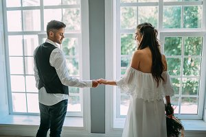 Charming bride and groom are holding hands on panoramic window background. Back view. Wedding indoors, Soft focus on hands