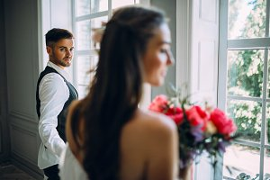 Handsome groom standing near the window look on his beautiful bride. Selective focus on the man. A Blurred bride with a bouquet. Man in the festive clothes near a panoramic window. Artwork