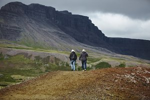 adult tourists walk along the trail among the lava field in Iceland