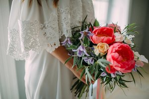 Bride holds in hands a rustic wedding bouquet with white roses and crimson peonies on window background. Close-up