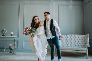 Cheerful bride and groom having fun together. Newlyweds laughing and go crazy. Artwork. Wedding indoors. Soft focus
