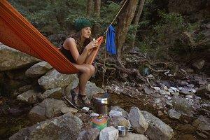 Woman having coffee while relaxing in hammock