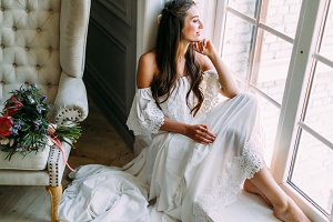 Woman by the window. Bride looking out the window, she waits for the groom. A bridal bouquet lies on the sofa.