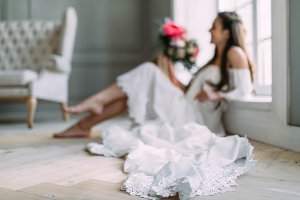 Blurred image of cheerful, young bride which holds a rustic wedding bouquet on panoramic window background. A happy girl with a bunch of flowers, selective focus on the lace of dress