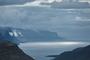 the austere Icelandic landscape with the mountains and the fjords in the background