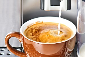 Coffee maker pouring milk coffee