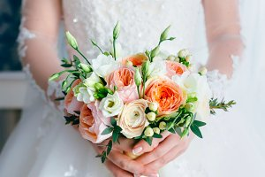 Beautiful bridal bouquet with white roses and peach peonies in a bride hands in white dress. Wedding morning. Close-up