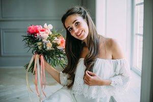 Beautiful young bride holds a rustic wedding bouquet with white roses and crimson peonies on window background. Close-up portrait. A happy girl with a bunch of flowers.