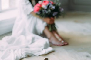 Wedding shoes on a blurred background of cheerful, young bride which holds a rustic bridal bouquet. A happy girl with a bunch of flowers, selective focus on shoes