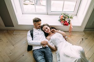Cheerful bride and groom holding hands and lie on the wooden floor near the panoramic window. Wedding morning