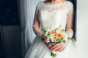 A beautiful bride is standing near the window and holding a wedding bouquet with white roses and peach peonies. Close-up