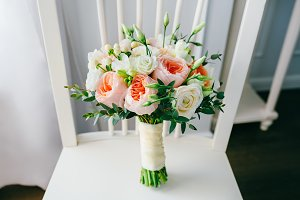 Wedding bouquet of flowers on the white wooden chair
