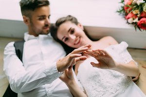 Blurred bride and groom holding hands and lie on the floor. Soft focus on the hands. Artwork. Wedding morning.
