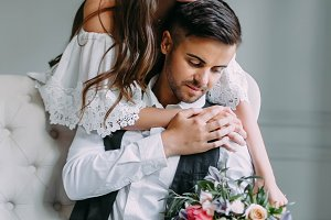 Cheerful bride hugging the groom. Newlyweds posing in luxury room. Soft focus