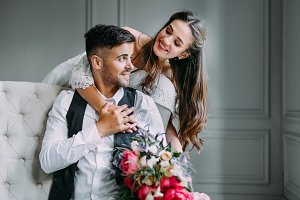 Cheerful bride hugging the groom. Newlyweds laughing and looking at each other. Artwork. Wedding. Soft focus