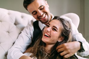 A young couple in love having fun on a sofa and playing with a hair of the girl. Cheerful bride and groom laughing, close-up. Soft focus on the girl