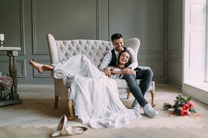 Young bride in tender lace dress lies on knees of a handsome groom in blue jeans. Cheerful newlyweds are laughing. Full length