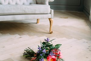 Rustic wedding bouquet with white roses, crimson peonies, and greens on a wooden floor.