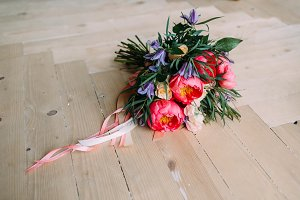 Rustic wedding bouquet with white roses, crimson peonies, and greens on a wooden floor. Close-up.