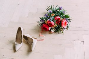 Rustic wedding bouquet with white roses, crimson peonies, and shoes on a wooden floor. Close-up.