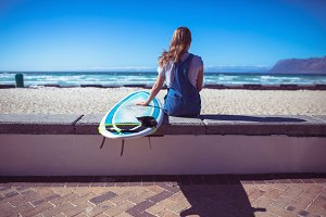 Female surfer sitting with surfboard and looking at the sea
